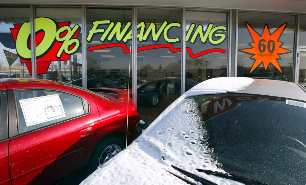 A car dealership advertising financing deals on the window