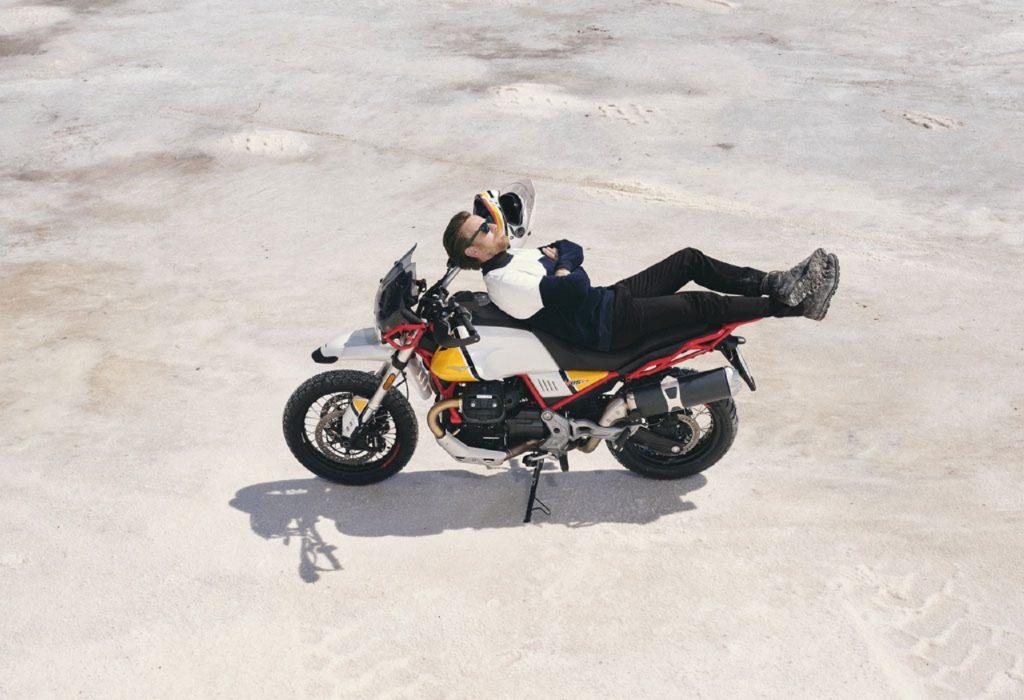 Ewan McGregor sitting on a white-and-yellow Moto Guzzi V85TT Adventure
