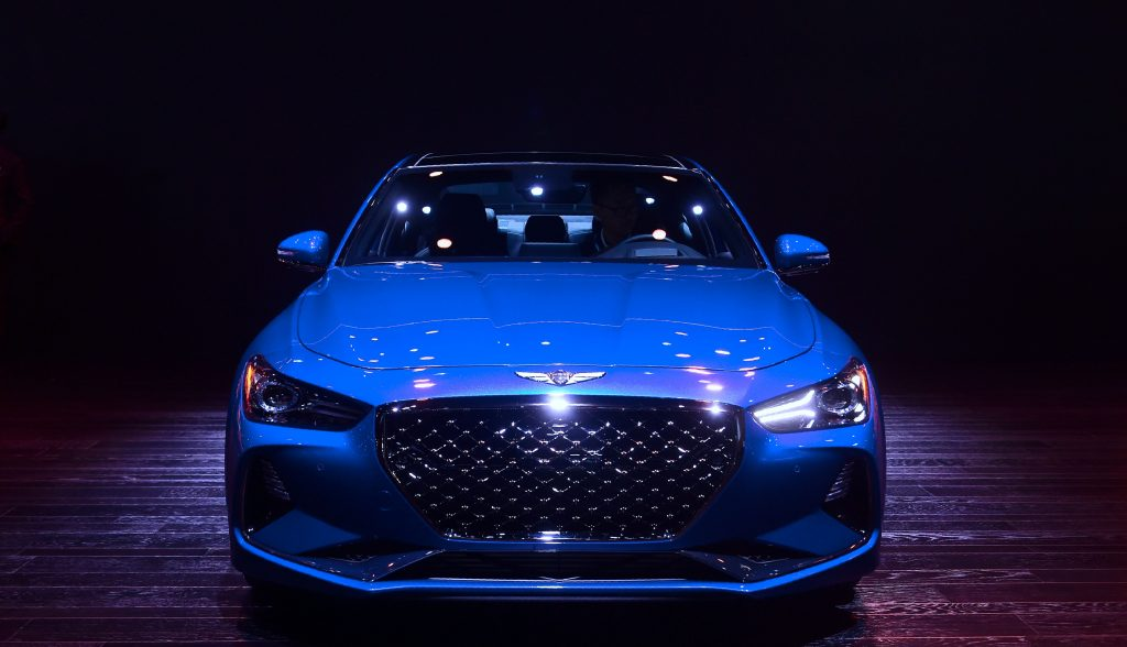 A Genesis G70 on display encased by a shadow
