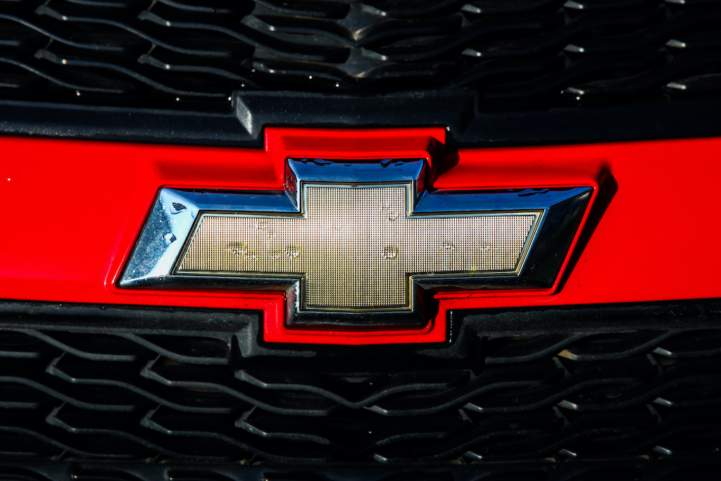 A close image of Chevy's bowtie logo on the front of one of their vehicles.