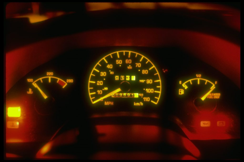 An instrument cluster is glowing with lighting at night time.