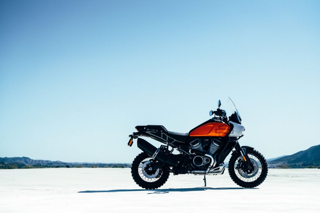 An orange-tanked Harley-Davidson Pan America concept parked on a dry lakebed