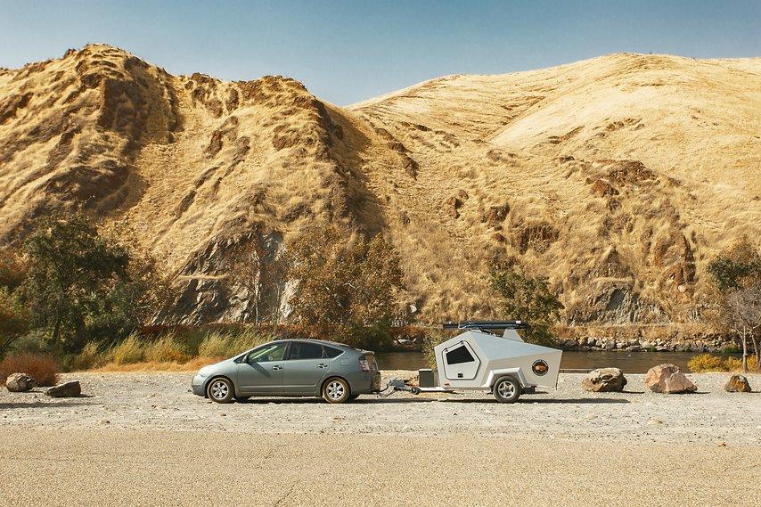 A Toyota Prius hauling a Polydrop RV camper.