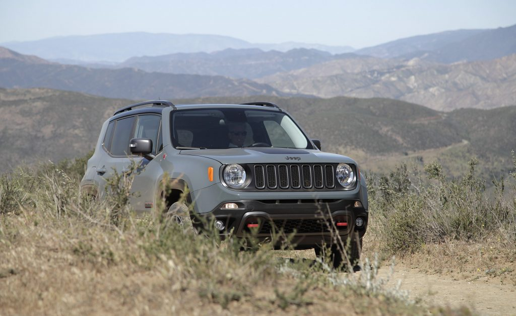 A Jeep Renegade Trailhawk drives down a dirt road