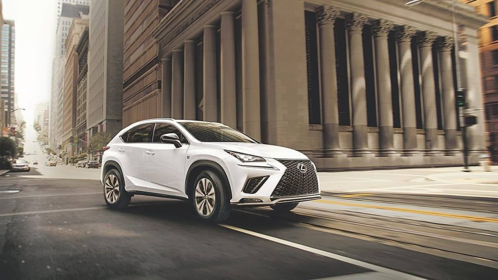 A white 2020 Lexus NX driving down city streets.