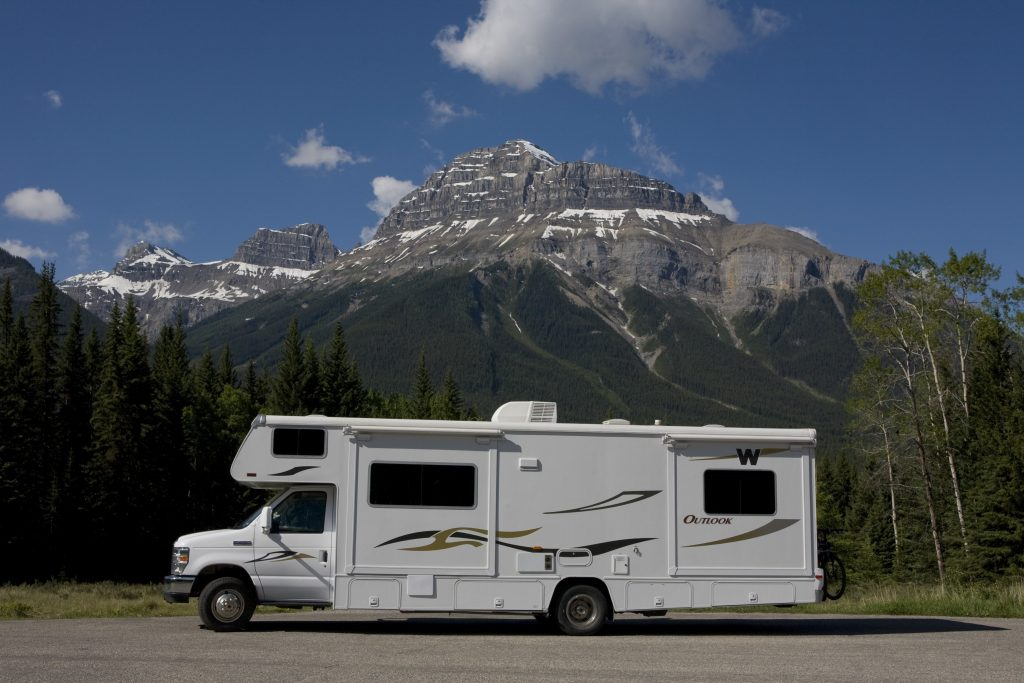 A motorhome RV camper parked on a road in front of a mountain