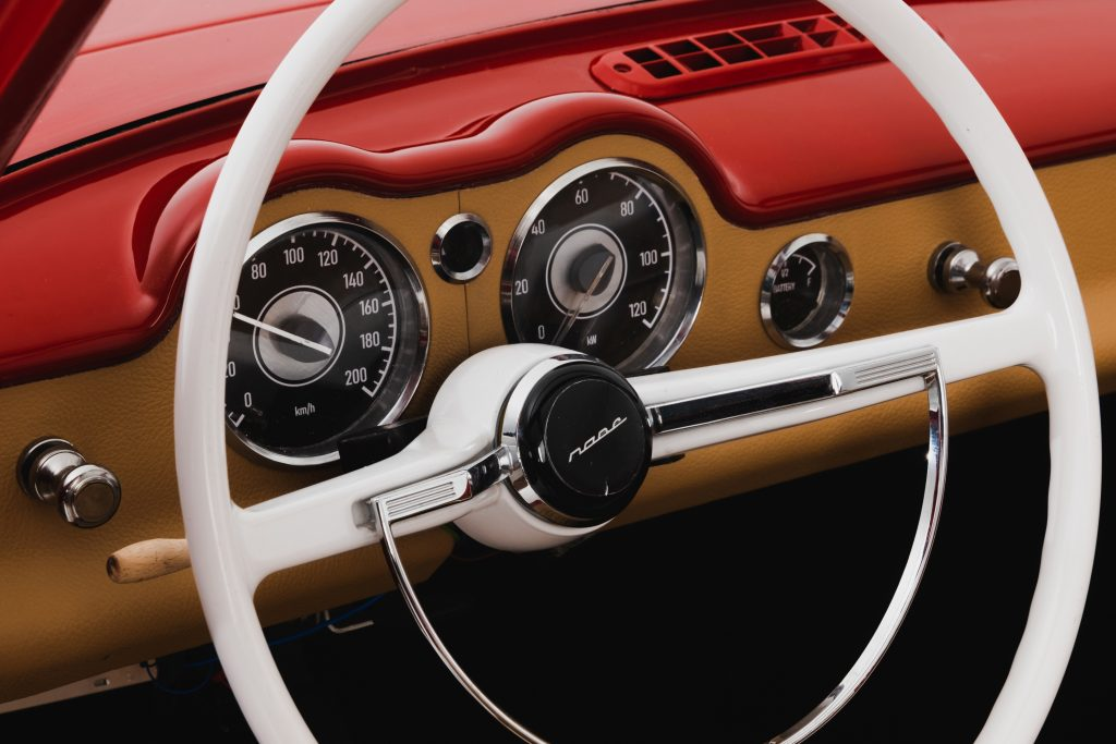 The white steering wheel and the dash instruments are shown from the Nobe GT100.