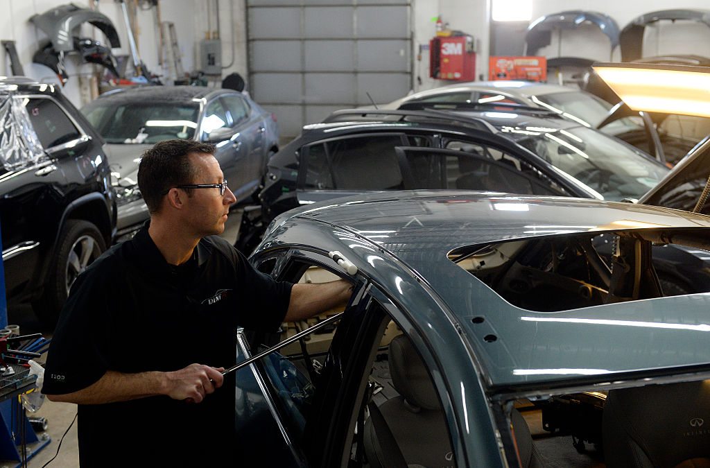 ENGLEWOOD, CO - JANUARY 22: Auto body shops in the Denver metro area are packed with cars. Cars with hail damage from last year and cars needing repair from the winter collision season have filled the garages. At Hampden Auto Body in Englewood, CO Eric Nelson a paintless dent specialist pops dents out of the roof of a car with with hail damage on Thursday, January 22, 2015. (Photo by Cyrus McCrimmon/The Denver Post via Getty Images )
