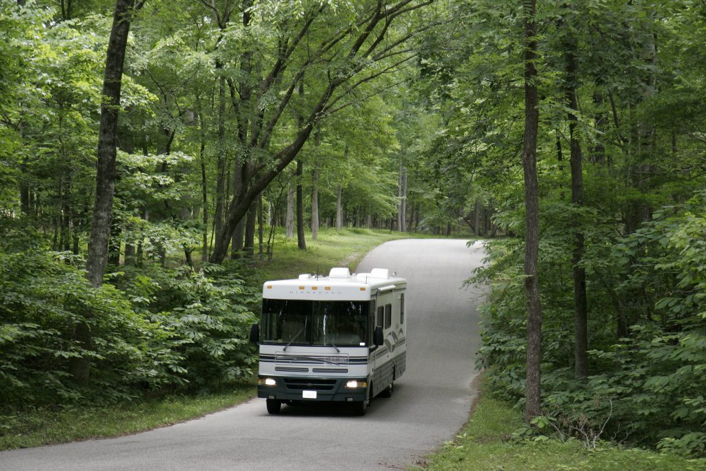 An RV driving down a road in the woods