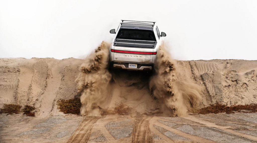 A white Rivian R1T climbs a South American sand dune