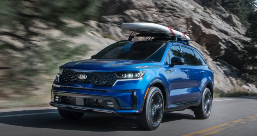 a blue 2021 Kia Sorento hybrid crossover SUV driving at speed in the mountains