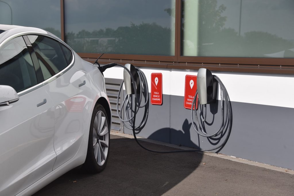 A Tesla Model 3 is charged at the charging station for TESLA electric vehicles, manufacturer of electric vehicles