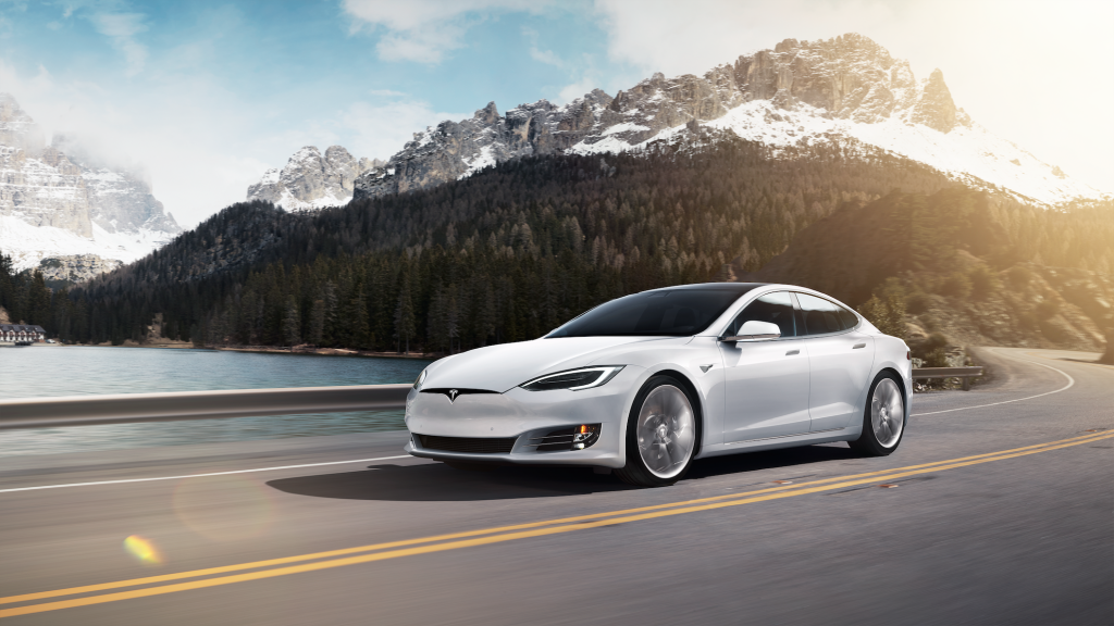 White Tesla Model S driving through the mountains
