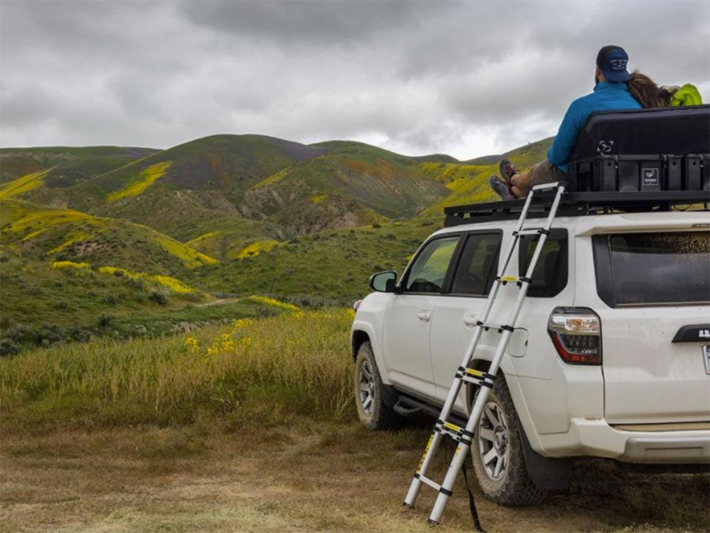 A man sits on the roof rack of a white Toyota 4Runner with a Front Runner aluminum telescopic ladder