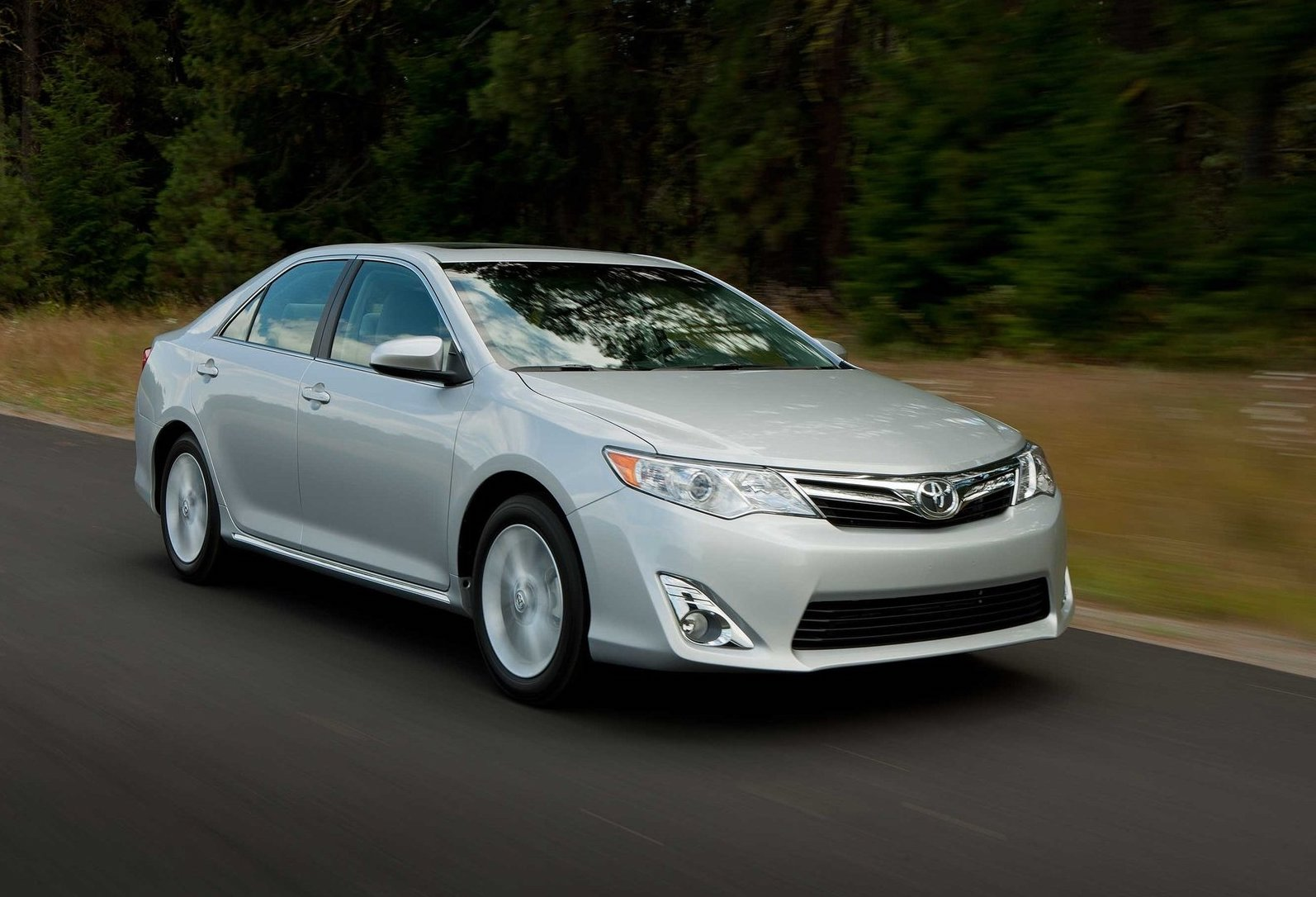 A silver 2012 Toyota Camry driving at speed on a scenic road near an evergreen forest.