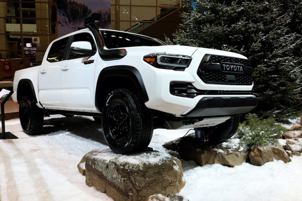 A white Toyota Tacoma displayed at an auto show.