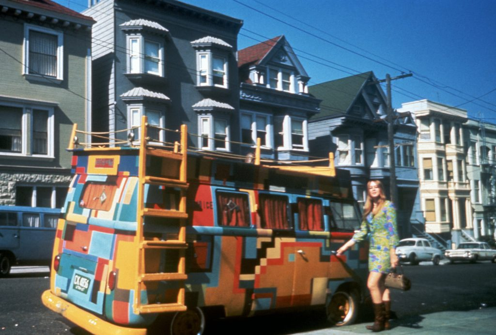 A hippie girl stands next to a Volkswagen bus painted in a bold design, San Francisco, California, July, 1967.
