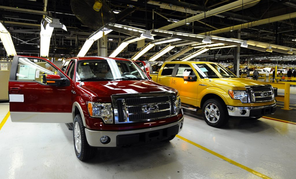 Two Ford F-150 trucks next to an assembly line