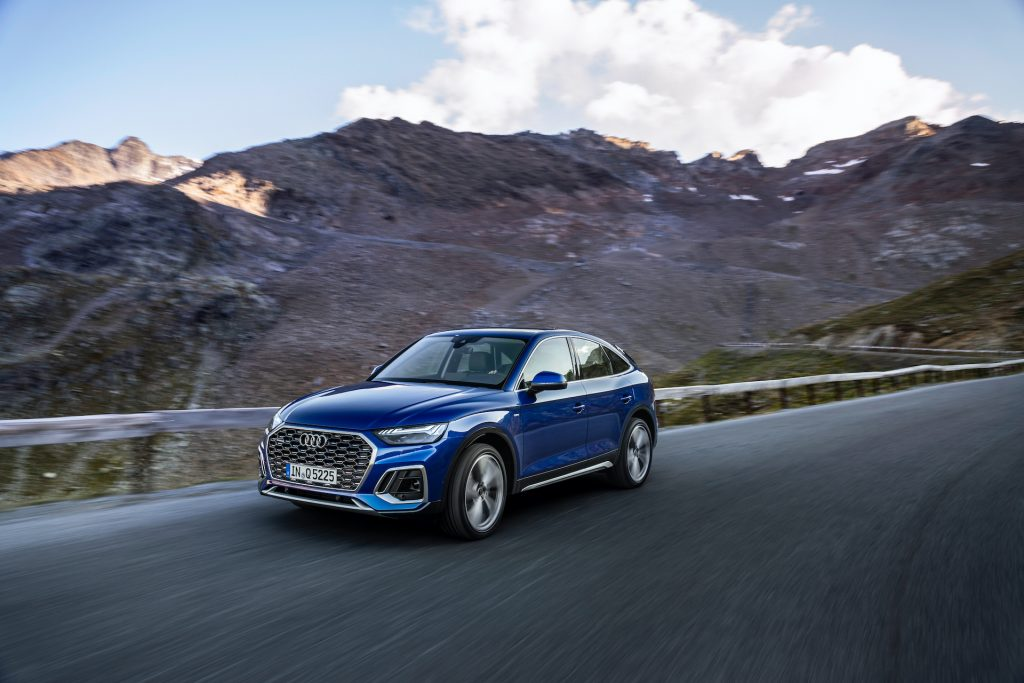 An electirc blue 2021 Audi Q5 Sportback driving on the countryside.