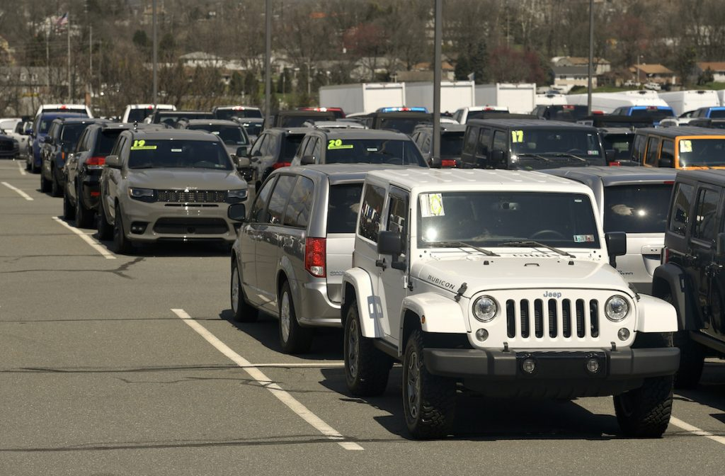 car dealership lot with a white jeep and other cars with model years and prices highlighted