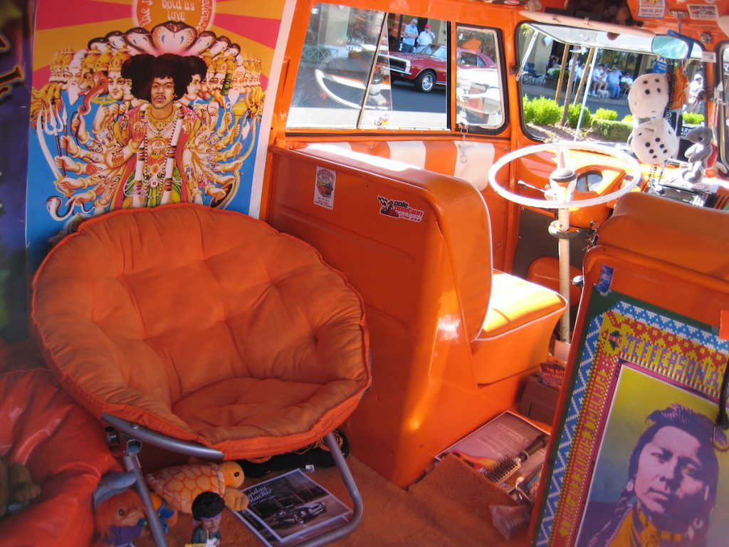 Inside a hippie van RV with orange decor and a Jimi Hendrix poster