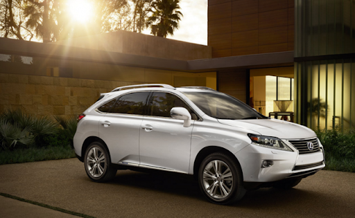 A white 2015 Lexus RX Hybrid parked in a sunny driveway.