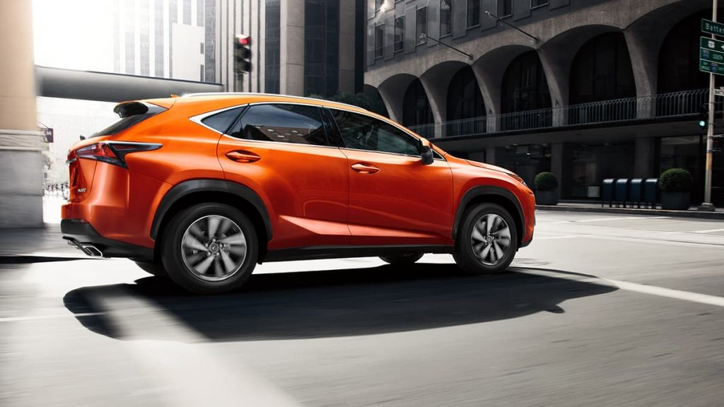 a cadmium orange lexus nx 300 f sport driving in the city