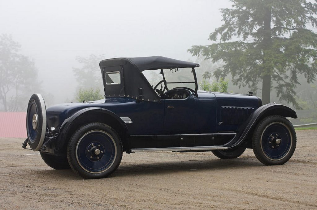 The rear 3/4 view of a blue 1924 Wills Sainte Claire Model A-68 Roadster in a foggy forest