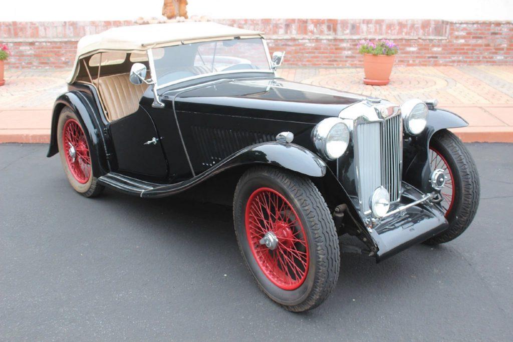 A black 1936 MG TA by a brick wall