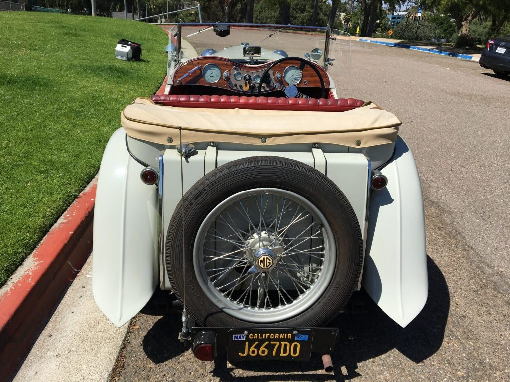 The rear view of a gray 1949 MG TC EXU with a view of its red-leather interior