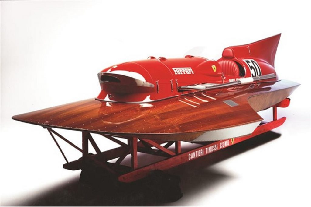 The red-and-mahogany 1952 Ferrari Arno XI hydroplane on its stand