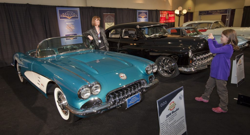 A light blue 1958 Chevrolet Corvette C1 displayed at an auto show. Two other classic cars are pictured to the right of it.