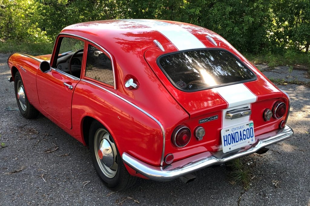 The rear 3/4 view of a red-with-white-stripes 1966 Honda S600 coupe