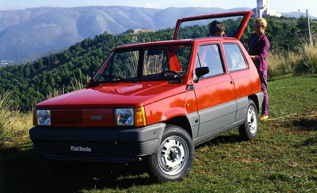 A red 1980 Fiat Panda parked on a grassy hill with its hatchback raised