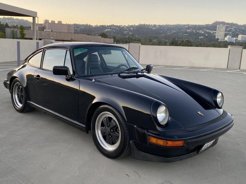 A black 1982 Porsche 911 SC on a parking garage roof