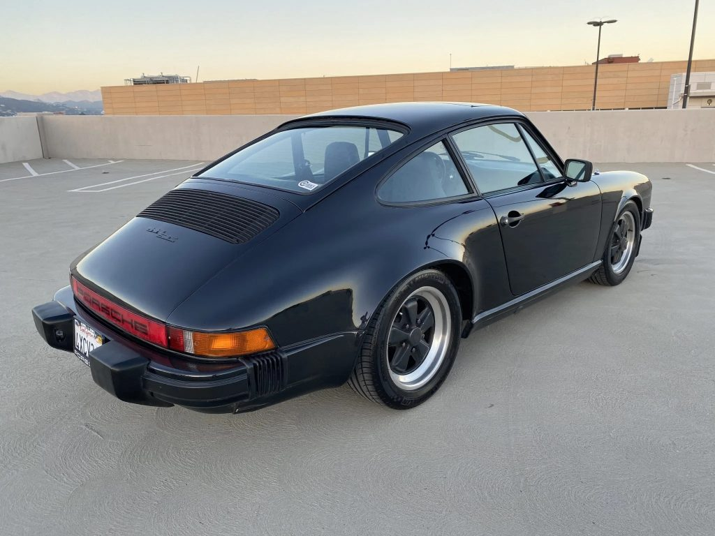 The rear 3/4 view of a black 1982 Porsche 911 SC on a parking garage roof