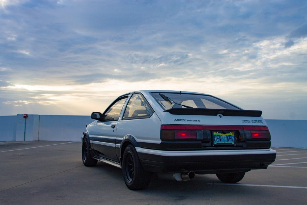 The rear 3/4 view of a black-and-white 1986 JDM Toyota AE86 Sprinter Trueno on a parking garage roof