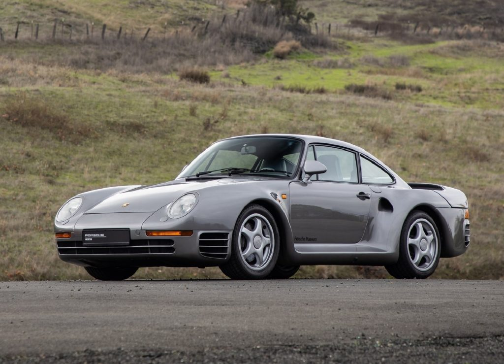 A gray 1986 Porsche 959 parked near a grassy hill