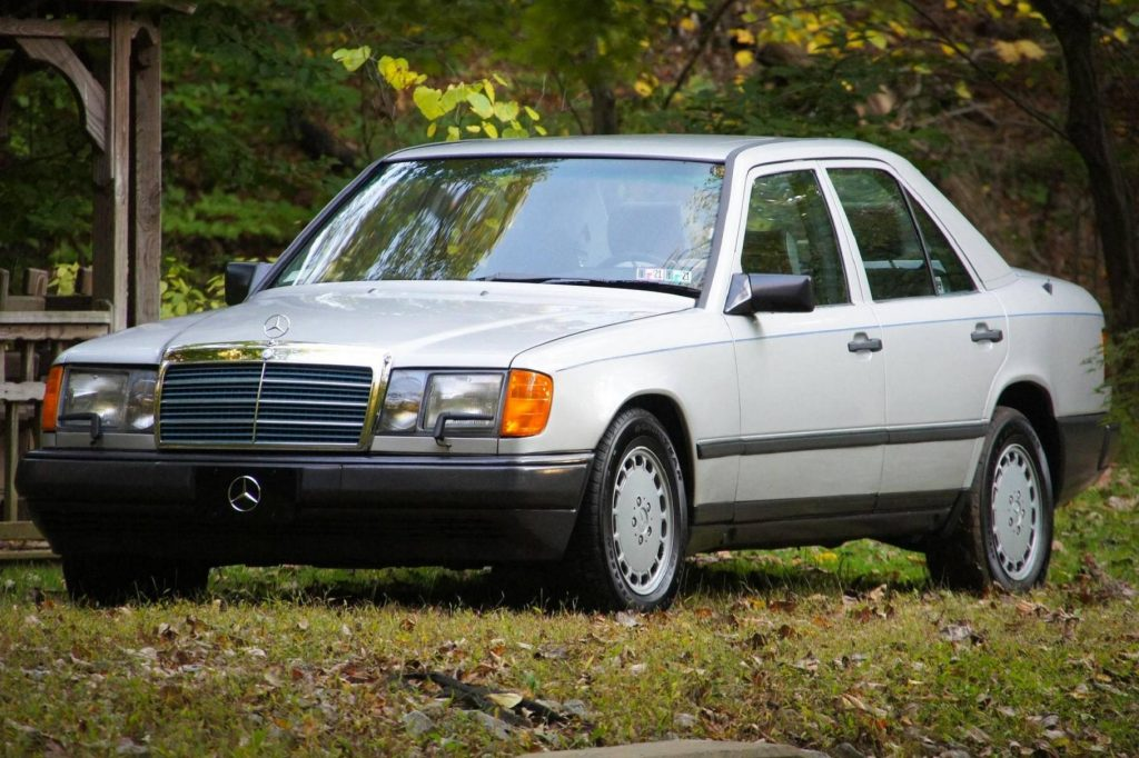 A silver 1986 W124 Mercedes-Benz 300E in the forest