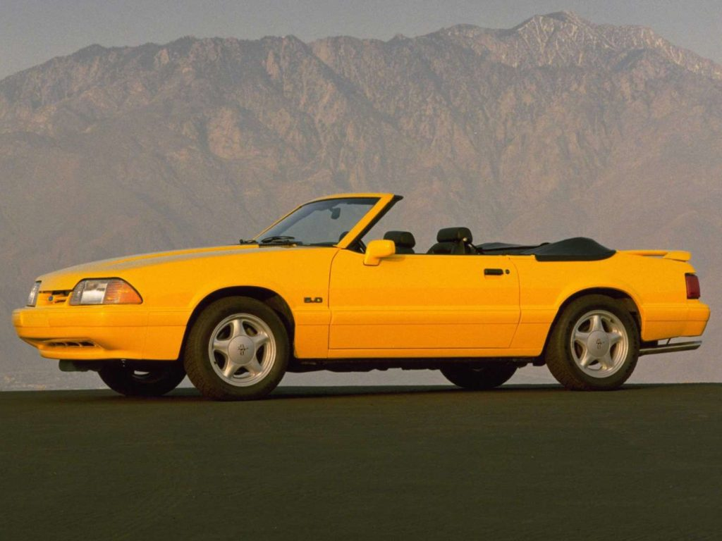 A yellow, convertible 1993 For Mustang sits at the base of a mountain with its top down.