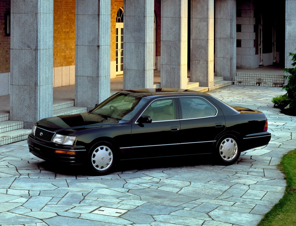 A black 1994 Toyota Celsior next to a regal building