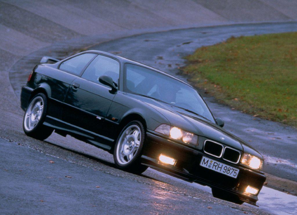 A green 1995 BMW E36 M3 GT drives around a wet racetrack