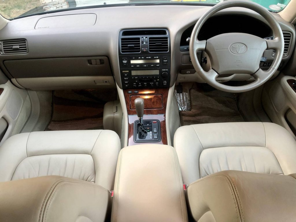 The tan-leather and wood-trimmed front interior of a 1995 Toyota Celsior