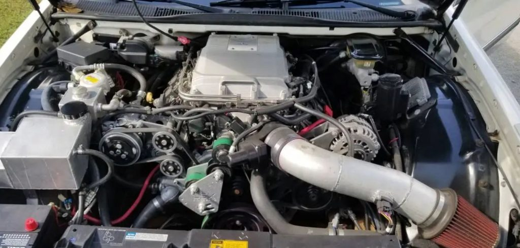 The engine bay reveals a custom crate engine for a Cadillac Fleetwood Brougham