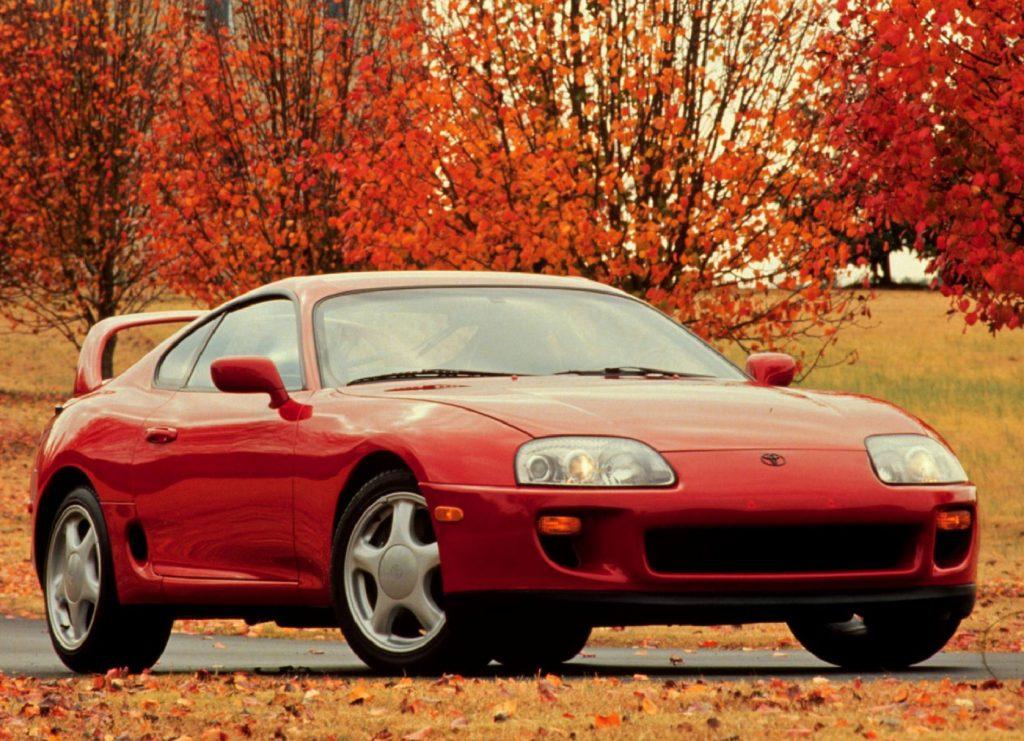 A red 1996 Toyota Supra among orange-colored fall foliage