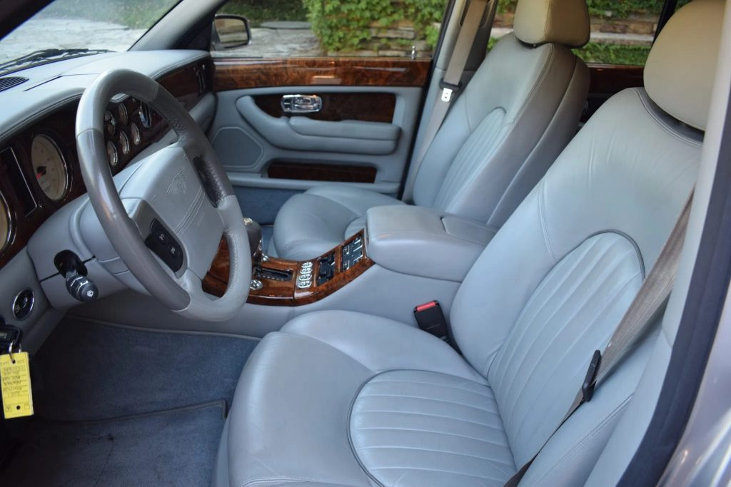 The gray-leather-upholstered front seats and wooden dashboard of a 2001 Bentley Arnage Red Label