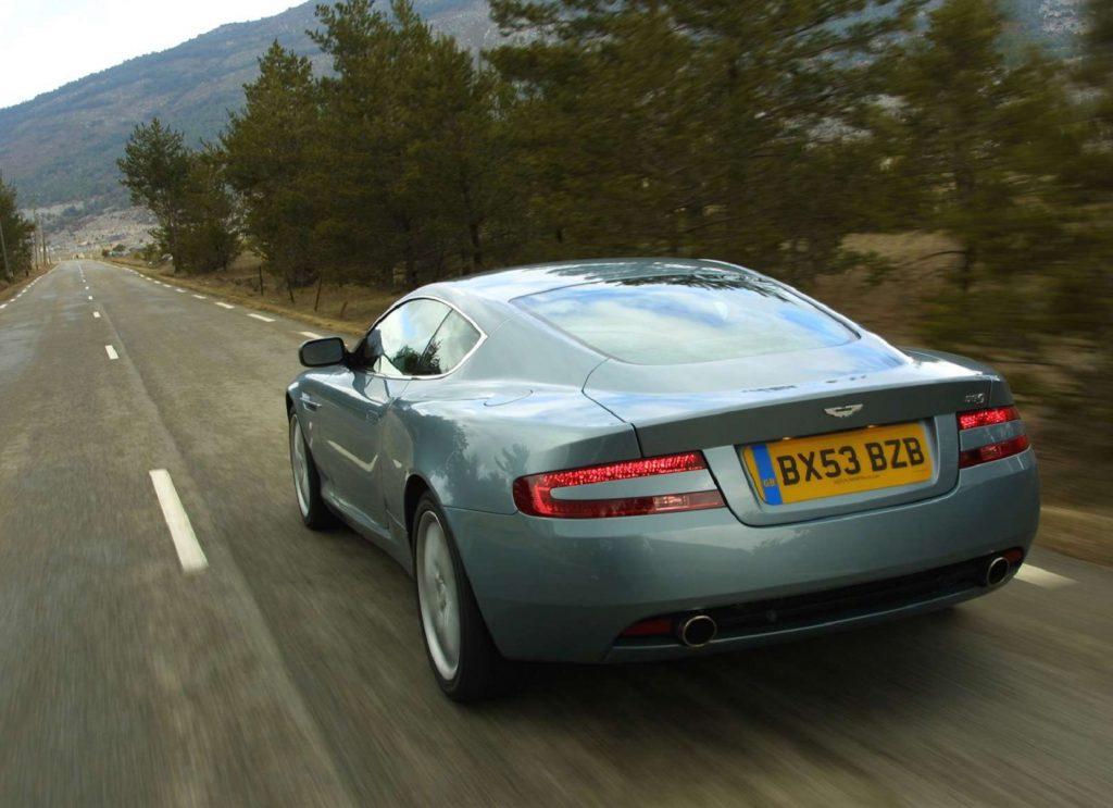 A silver 2004 Aston Martin DB9 drives down a road