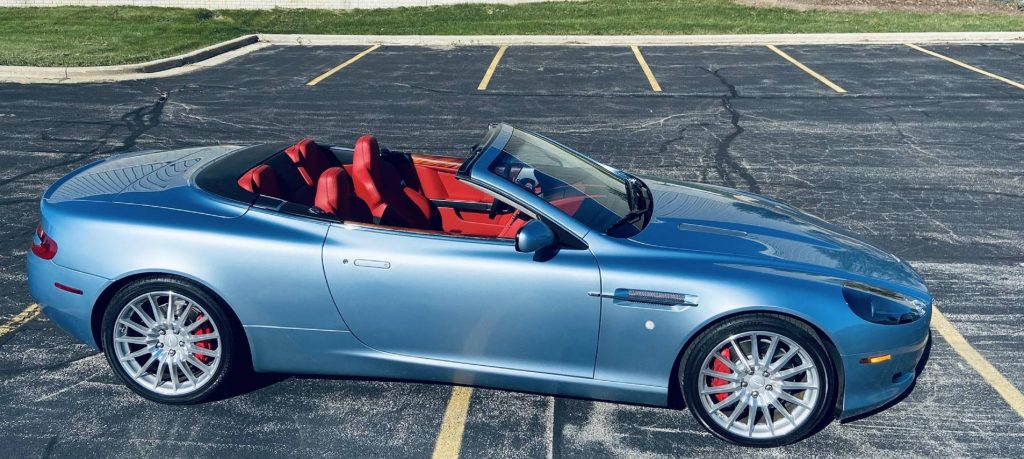 The side view of a blue 2006 Aston Martin DB9 Voltante with its top down