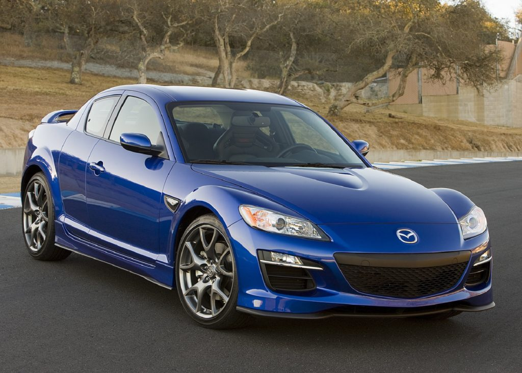A blue 2009 Mazda RX-8 on a racetrack