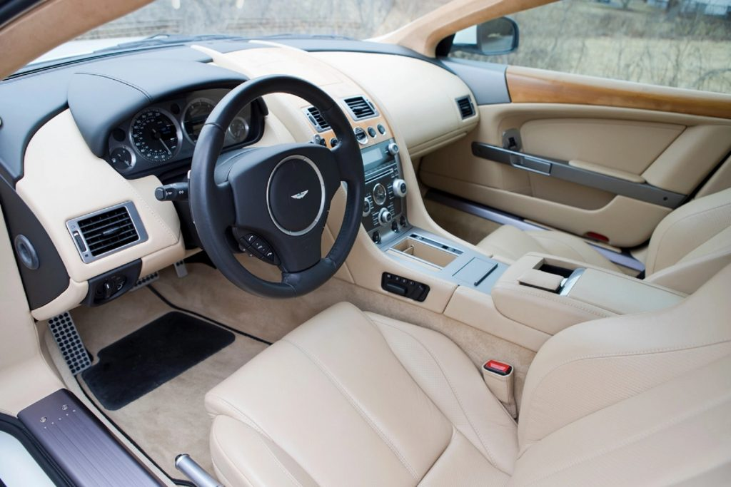 The tan-leather-upholstered interior of a 2010 Aston Martin DB9